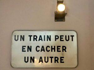 """Panneau """"Un train peut en cacher un autre"""" - Train Hostel Bruxelles Belgique"""