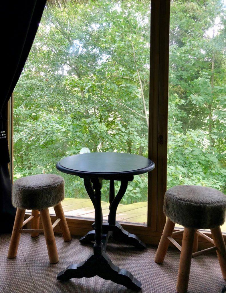 Port-le-Grand Chateau des Tilleuls - cabane Nid Chouette intérieur table et tabourets